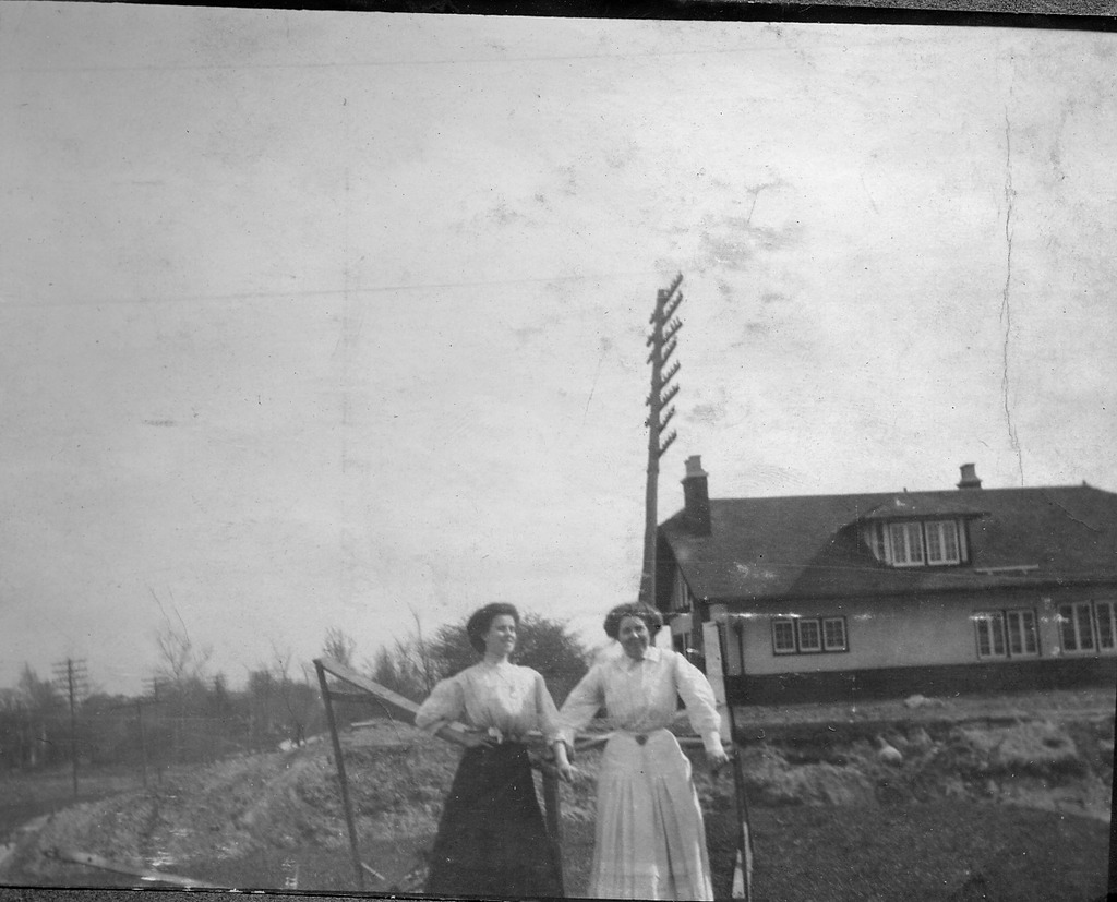 2 ladies in front of house with large electric pole