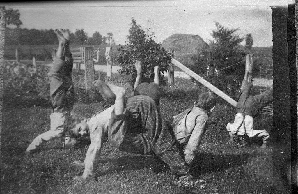 2 boys standing on head and 2 in front doing acrobatics