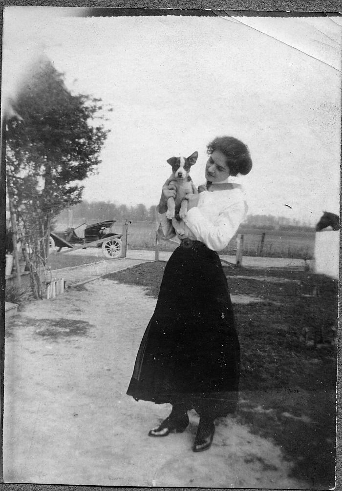 Lady with puppy - old car in background