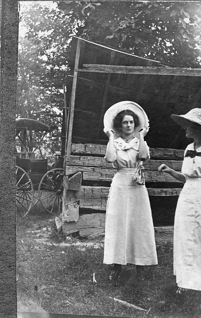 2 ladies with hats, front of old shed, buggy beside shed