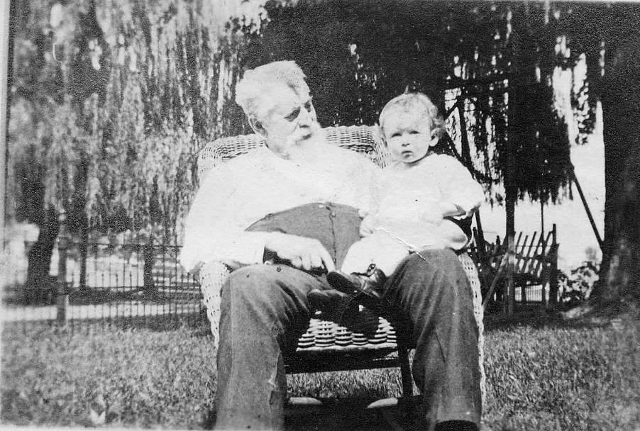 Man in wicker chair holding young child