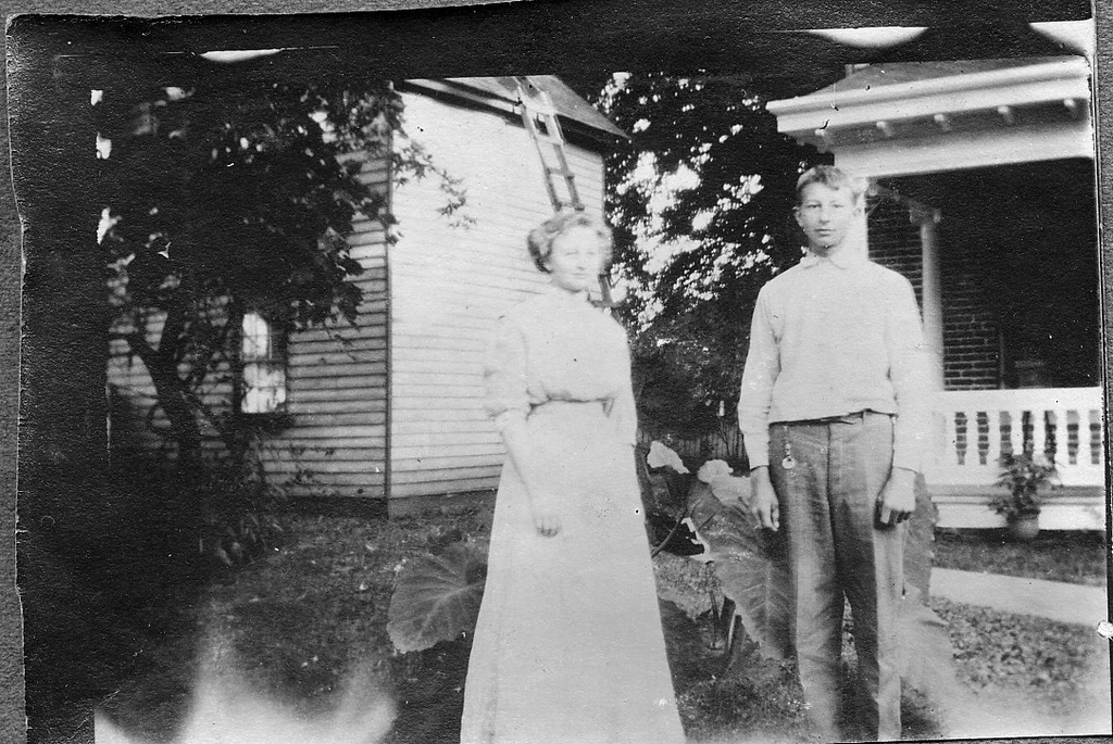 Man and woman on front porch of house