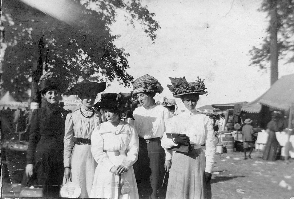 Five ladies wearing hats at a fair? Tents in background.