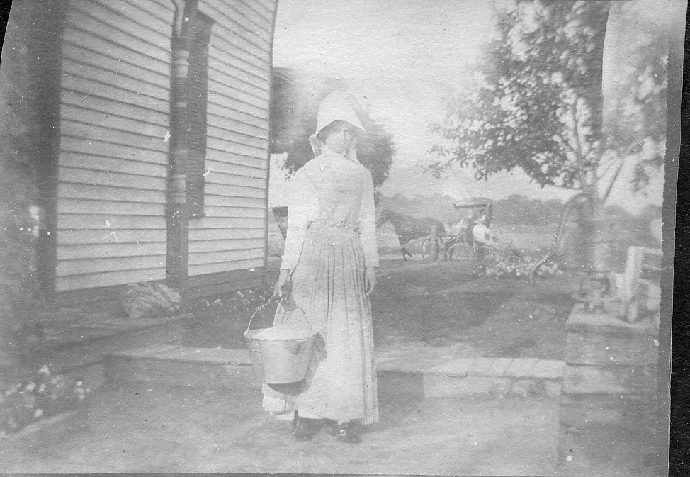 Lady with sunbonnet, background is horse and buggy
