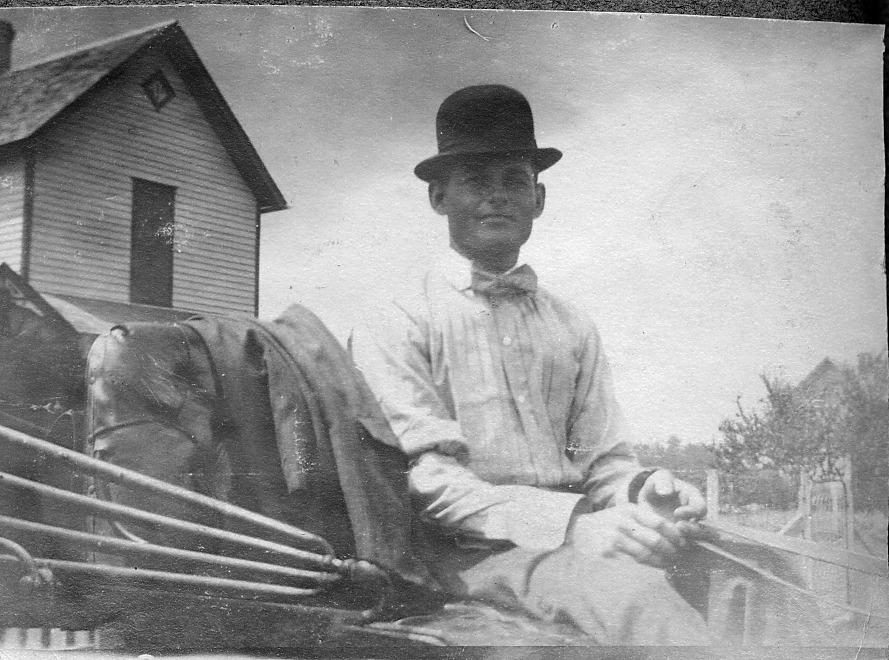 Man on wagon seat wearing derby