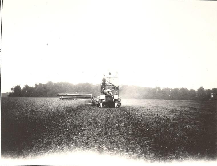Farm machine and 2 men harvesting