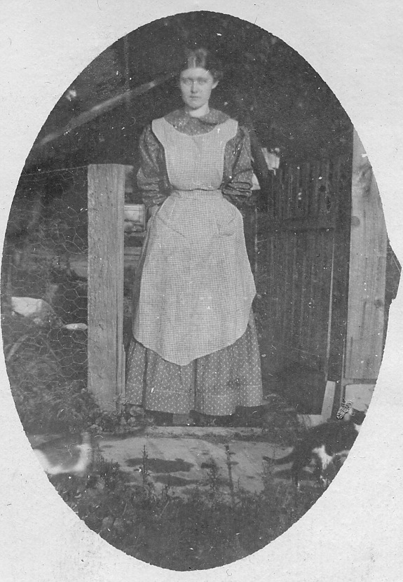 Lady standing in gate, oval picture
